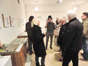 """Bildmitte: Klaus Urbons mit dem """"Zauberstab"""" - in der Ausstellung von Peter Helmke"""